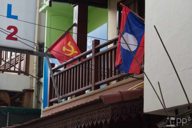 Wooden second story porch with the Laos and Communist flag flying outside