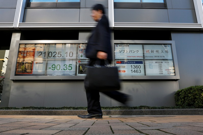 A man walks past in front of a stock quotation board showing the price of the SoftBank Corp. and Nikkei share average outside a brokerage in Tokyo