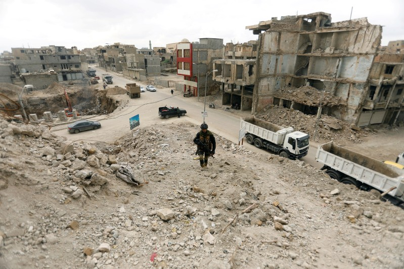 FILE PHOTO: A member of the Iraqi security forces passed by bridges destroyed in the war with Islamic State, in the Old City of Mosu