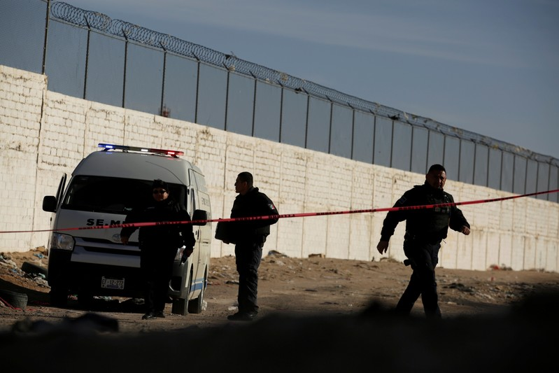 Forensic technicians work at a crime scene where a mutilated body was left by unknown assailants in Ciudad Juarez