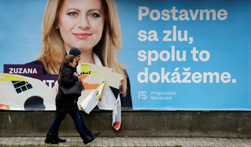 People walk past an election poster in Bratislava