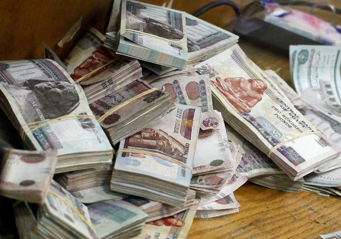 Stacks of money are pictured as an employee counts them at a bank in Cairo