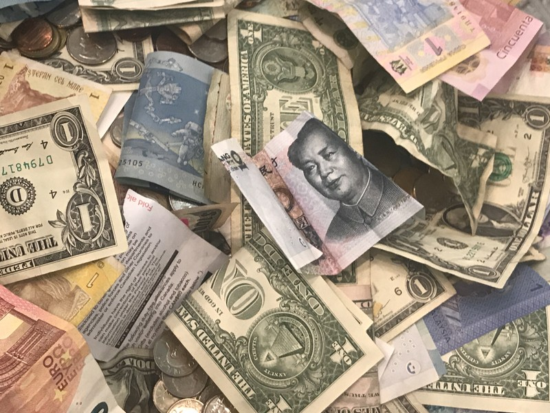 FILE PHOTO: U.S. dollars and other world currencies lie in a charity receptacle at Pearson international airport in Toronto