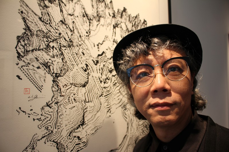 Hong Kong artist Victor Wong stands next to an artwork from his exhibition 'Far Side of the Moon' at 3812 Gallery in London