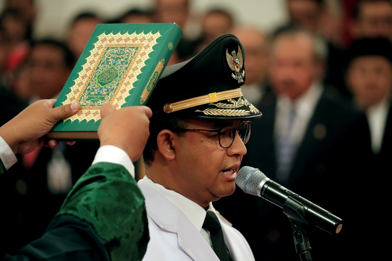 FILE PHOTO: A man holds a Koran as Jakarta Governor Anies Baswedan stands during a swearing-in ceremony at the Presidential Palace in Jakarta
