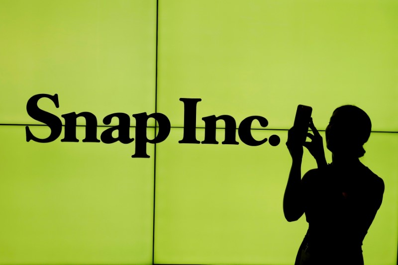 FILE PHOTO: A woman stands in front of the logo of Snap Inc. on the floor of the New York Stock Exchange in New York City