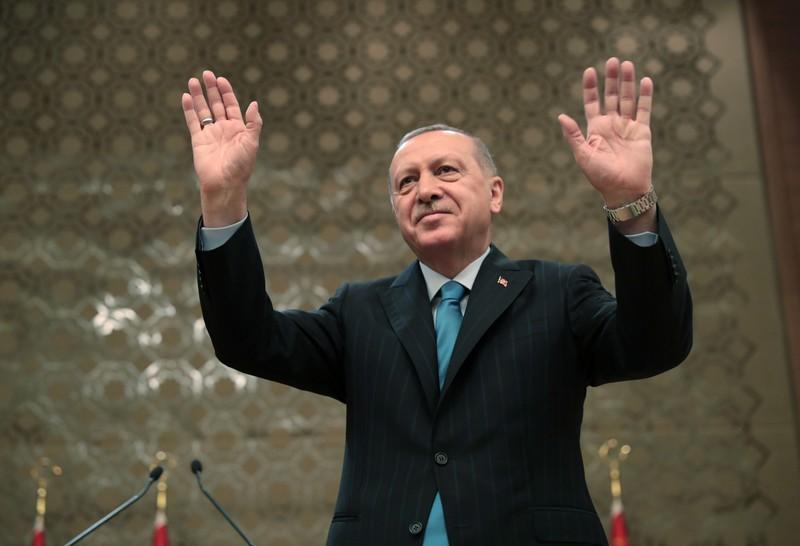 Turkish President Erdogan greets the audience during a meeting in Ankara