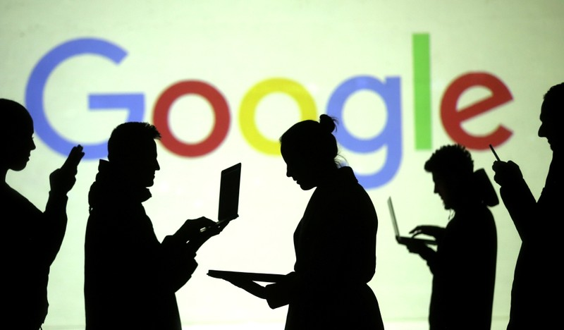 Silhouettes of laptop and mobile device users are seen next to a screen projection of Google logo in this picture illustration