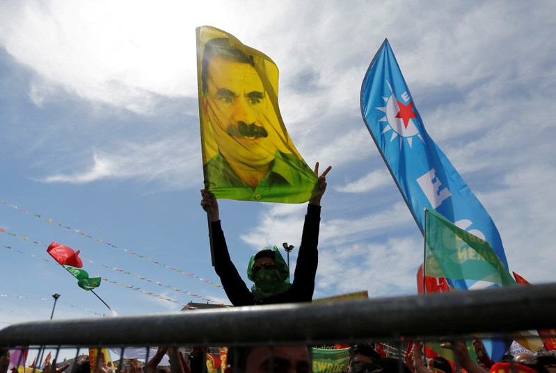 FILE PHOTO: A man holds a flag with a picture of imprisoned Kurdish rebel leader Ocalan during a gathering to celebrate Newroz, which marks the arrival of spring and the new year, in Istanbul