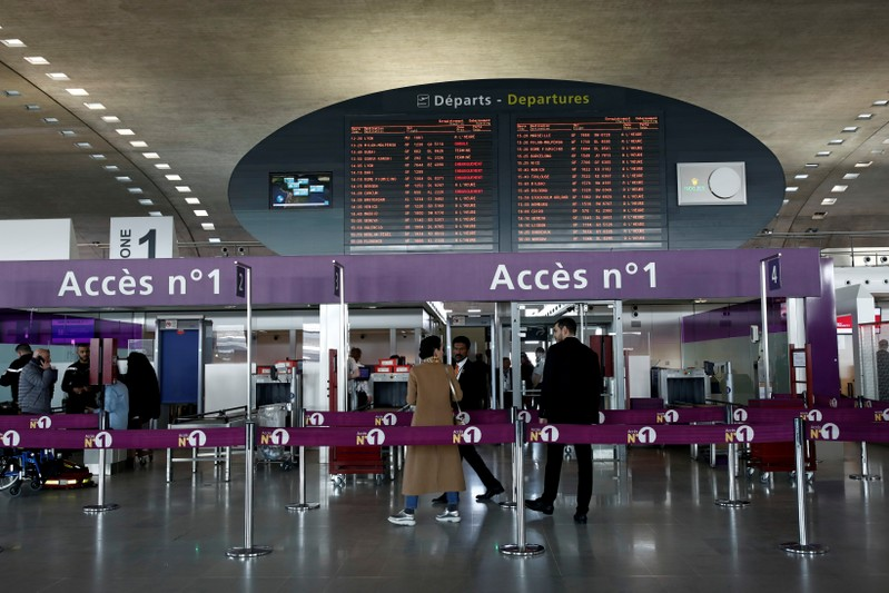 FILE PHOTO: Passengers gather in a departure hall as screens display flight information inside Charles de Gaulle airport, operated by Aeroports de Paris, in Roissy