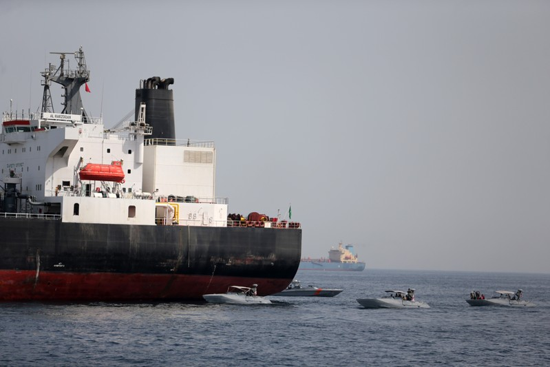 UAE Navy boats are seen next to Al Marzoqah, Saudi Arabian tanker, off the Port of Fujairah