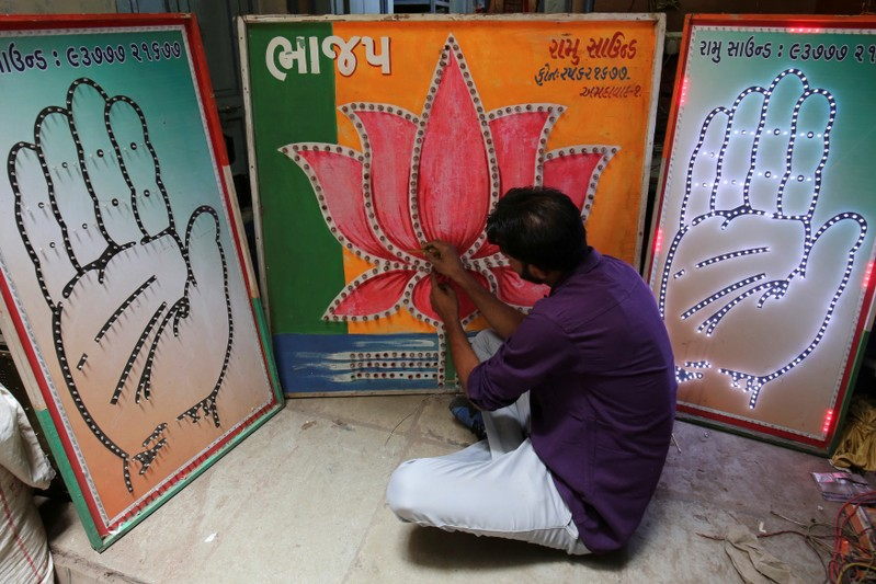 FILE PHOTO - An electrician tests LED-light fitted boards with symbols of India's ruling Bharatiya Janata Party and main opposition Congress party at a workshop in Ahmedabad