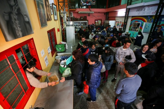 People line up to get stew ration at a soup kitchen in Buenos Aires