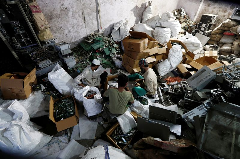 Men recycle e-waste from computers at a workshop in New Delhi