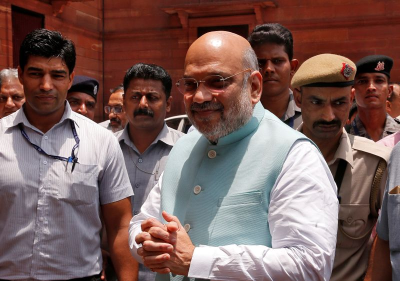 India's newly appointed Home Minister Amit Shah greets the media upon his arrival at the home ministry in New Delhi