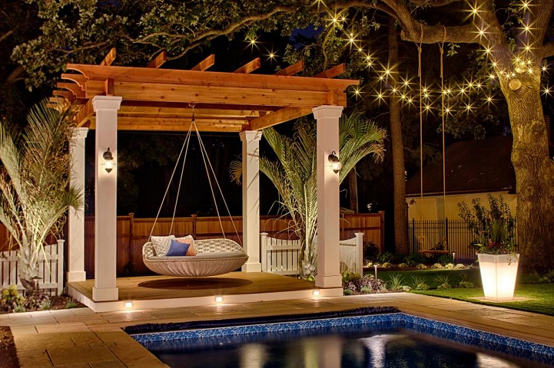 Pool area with swing bed at night