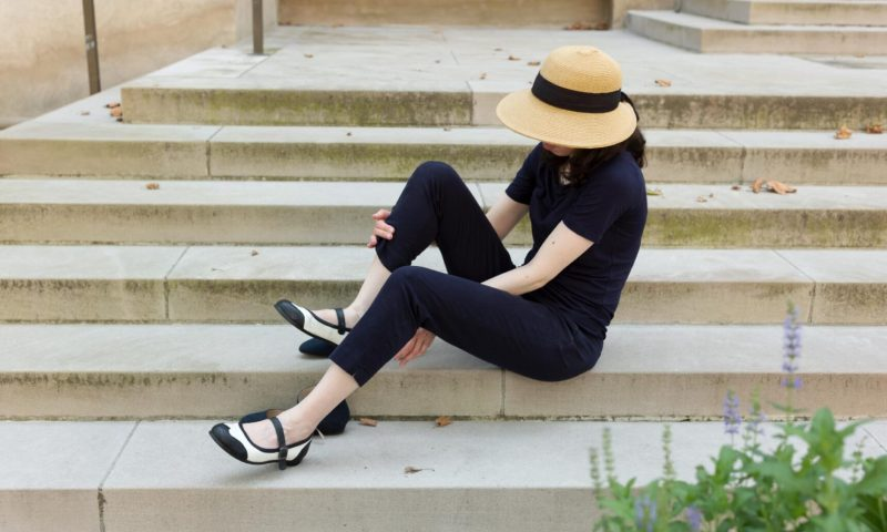 Engelhardt sitting on some stone steps, putting on a pair of black and white dance shoes.