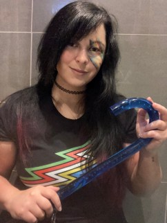 Ruthy is a white woman with long black hair. She is wearing a black t-shirt with the disability flag on it and has drawn the flag on her face in make-up. She is smiling and holding a blue walking stick.