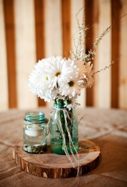 Think about reusing old glass bottles as a simple replacement for traditional vases.