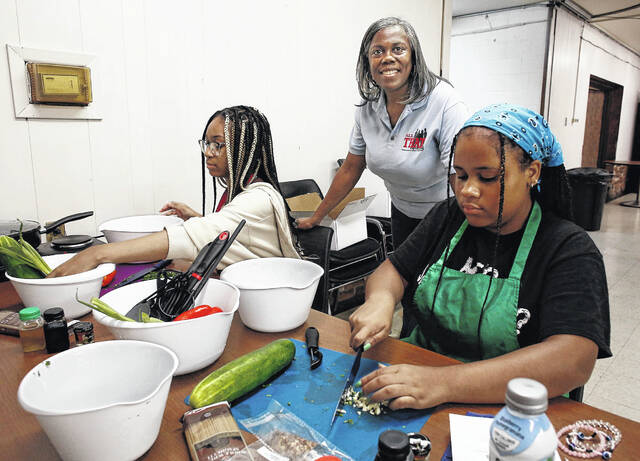 Danella Hicks, center, is founder and executive director of All THAT, an organization on the Eastside dedicated to mentoring under-resourced teens with academic help, career planning and life skills. She poses for a portrait at All THAT with Janese Carsby, 16, left, and Taylor Copas, 14, right, during a hospitality and culinary arts class on July 7, 2021.