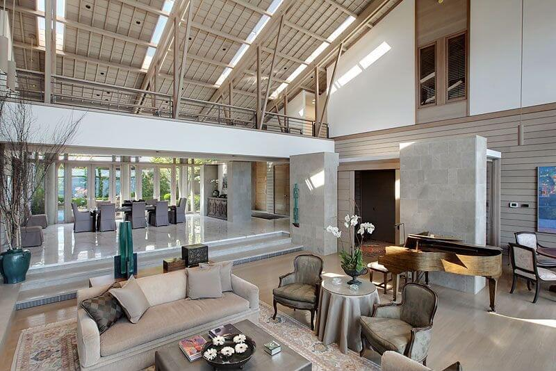 A gargantuan open living space with open walkway contributing dividing the space between living room and dining room