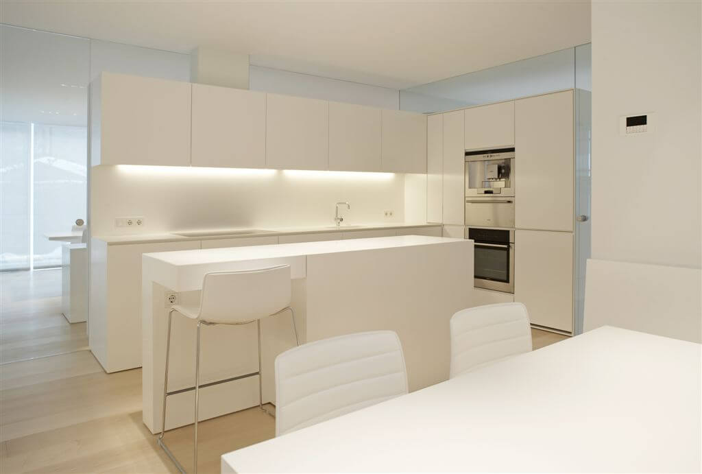Pure white cabinetry matches island, walls, and kitchen table set in this modern kitchen surrounded in mirrors over light hardwood flooring. Under-cupboard lighting illuminates countertops, while steel appliances punctuate the white.