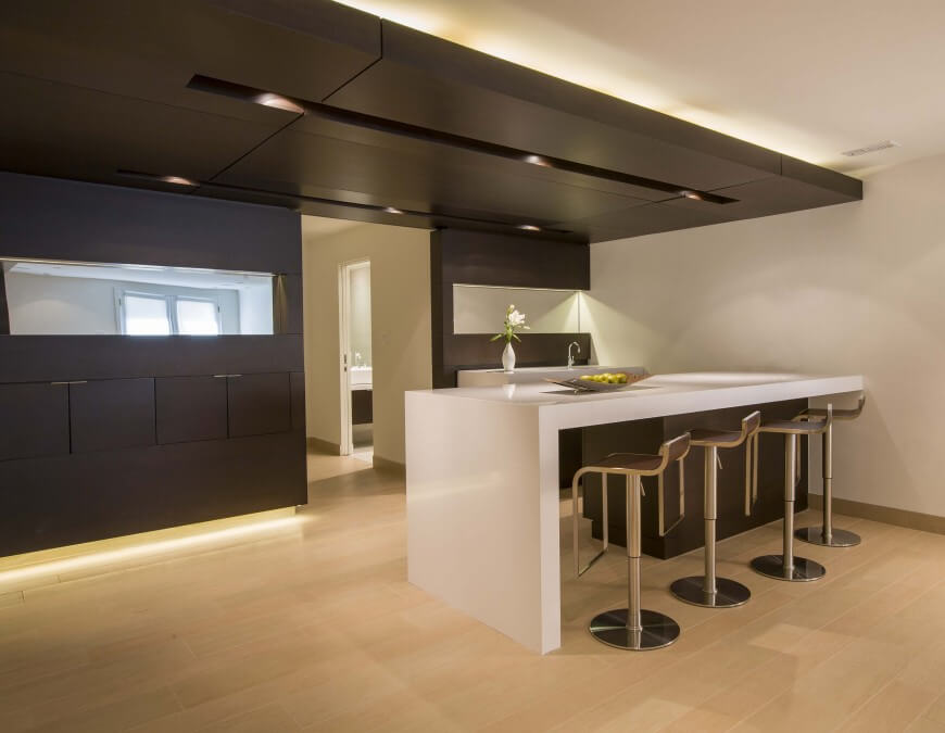 "Another truly modern kitchen design, here we see ""floating"" white island design over dark wood body on right, with matching dark wood cabinetry built into dividing wall, reaching up toward ceiling detail holding concealed lighting."