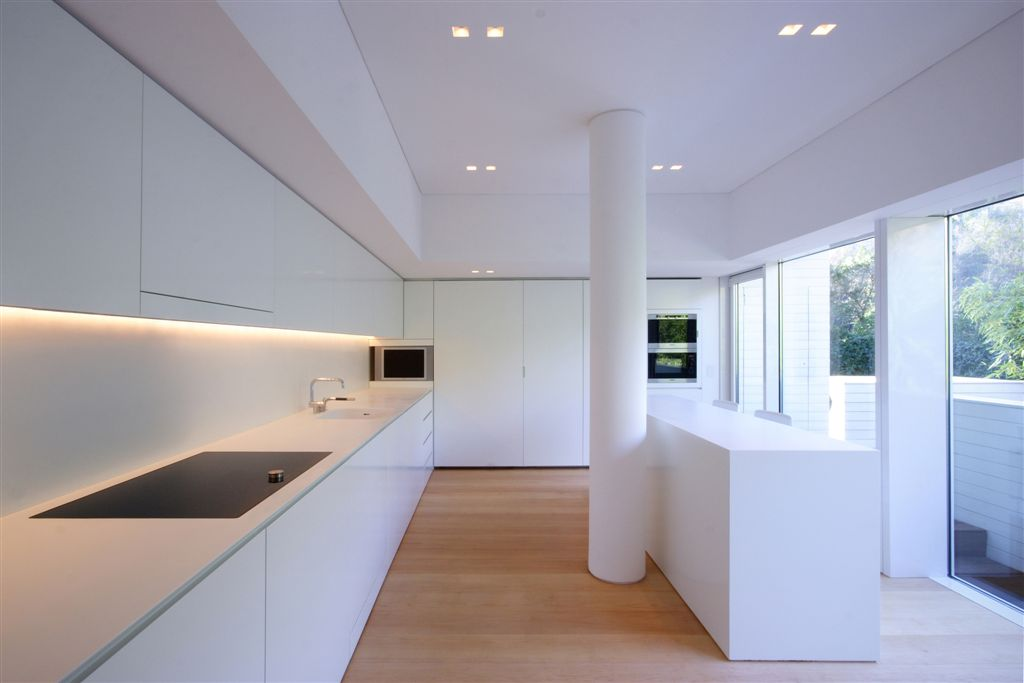 Ultra-minimalist design features throughout this home, including kitchen with bare, smooth white surfaces over natural hardwood flooring. All-white island, cabinetry, central pillar, and walls make for a bold, singular appearance next to floor to ceiling glass exterior.