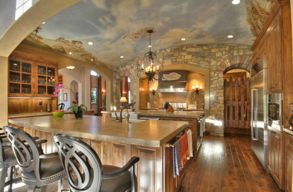Immense stone and wood kitchen features soaring, sky painted ceiling over rustic look space, with natural wood flooring, twin islands with stone countertops, and stone brick wall in background.