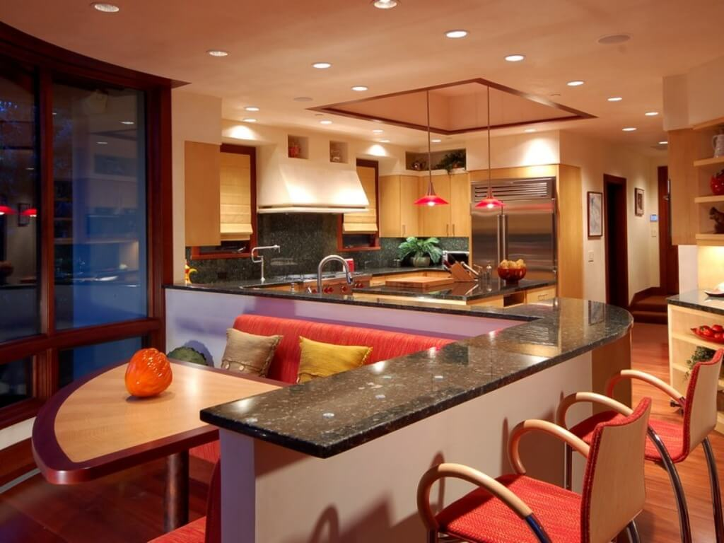 Moving further back in the same kitchen, we see a large L-shaped dining booth space in bright colors, with wraparound countertops surrounding, in a large open shared space.