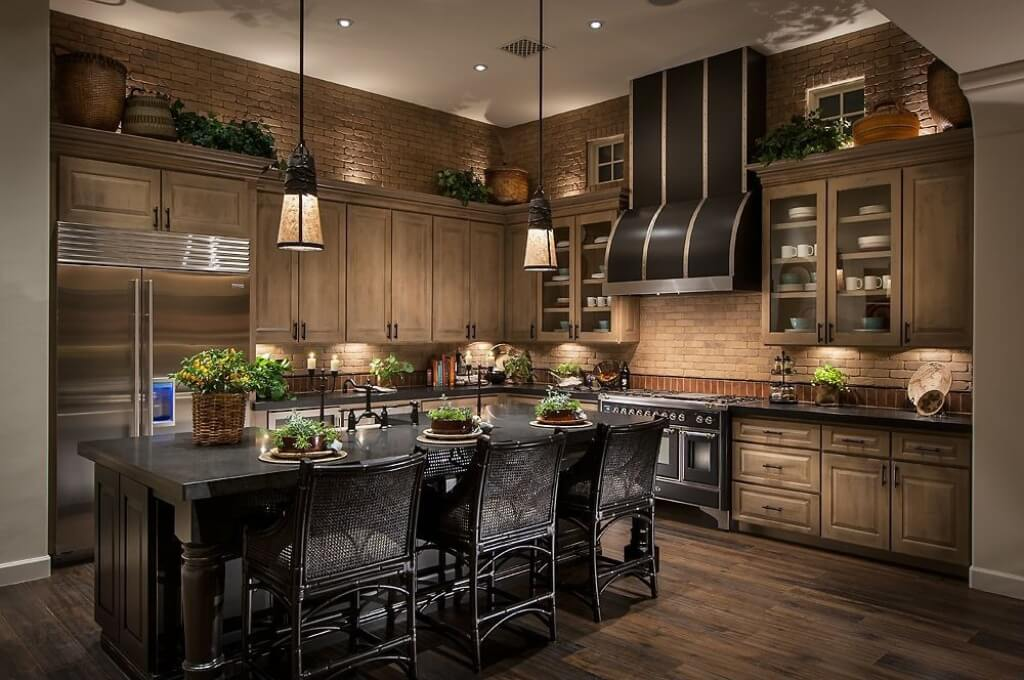 This large kitchen contrasts rich natural wood tones - hardwood flooring and cabinetry - with a large black wood island featuring full sink and dining space. Brown brick backsplash and upper walls are lit via lighting embedded above and below cabinets.