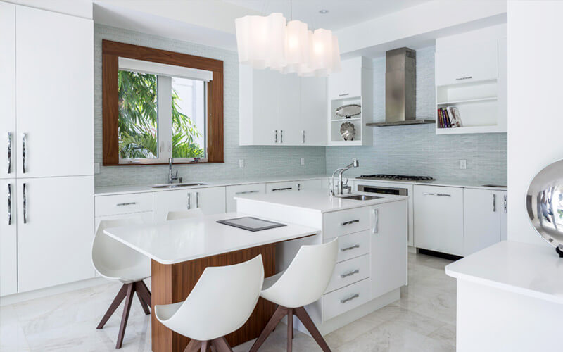 Here's a white kitchen of a different stripe. Two-tiered island features traditional segment with cupboards and sink, with attached dining table resting on natural wood base. Light blue tile backsplash surrounds white cabinetry throughout.