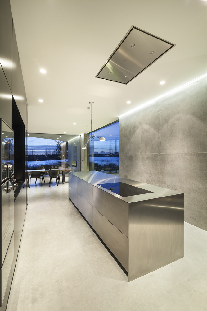 Bold, minimalist design rules this kitchen, a narrow passage between concrete wall and floor to ceiling black cabinetry housing most of the appliances and sink. Singular steel island with built in electronic range stands at center.
