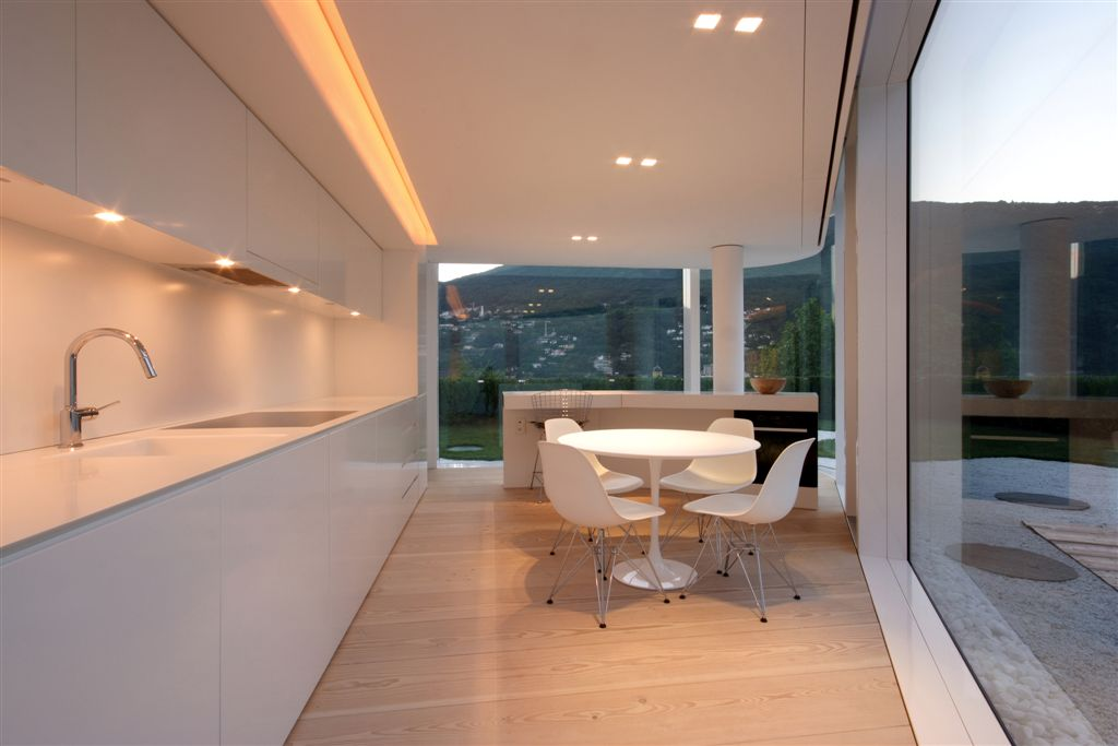 Uniquely shaped kitchen in white and natural wood holds a swath of white cabinetry and countertops, next to white dining table and island, wrapped entirely by floor to ceiling exterior glass.