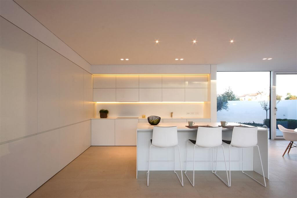 This modern kitchen in white features subtle under-cupboard lighting and large white island with dining space next to large sliding glass patio door. Beige tile flooring pairs with light tones for minimal contrast.