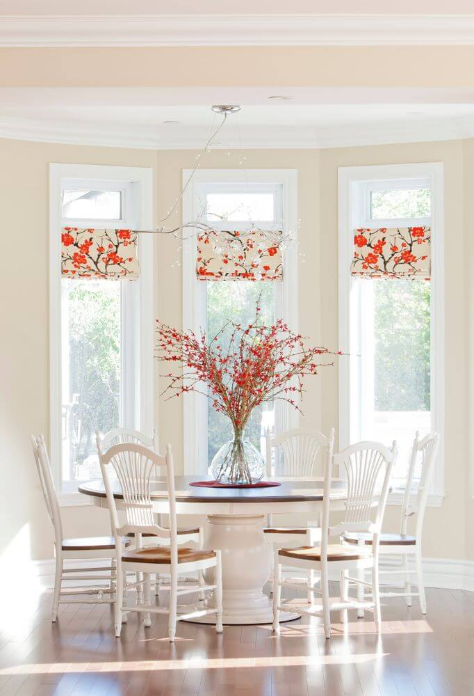 White and light wood dining set in front of three angled windows. Large red floral arrangement and dainty branch light fixture add an elegant touch.