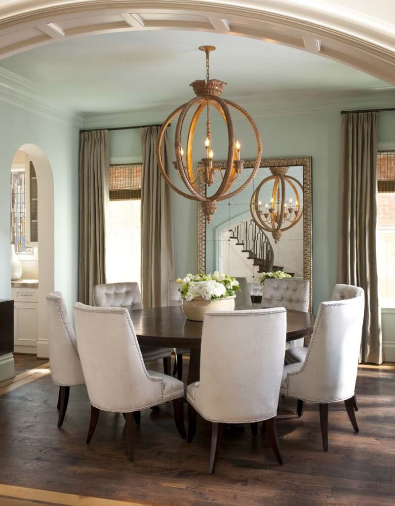 Plush dining chairs contrast with dark wood circular dining table. A large, gilded mirror reflects light around the room.