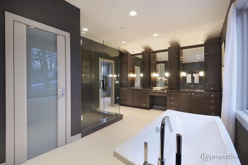 This enormous master bathroom features an entire wall of vanities with plenty of storage for every bit of product imaginable. Mirrors top each individual vanity.