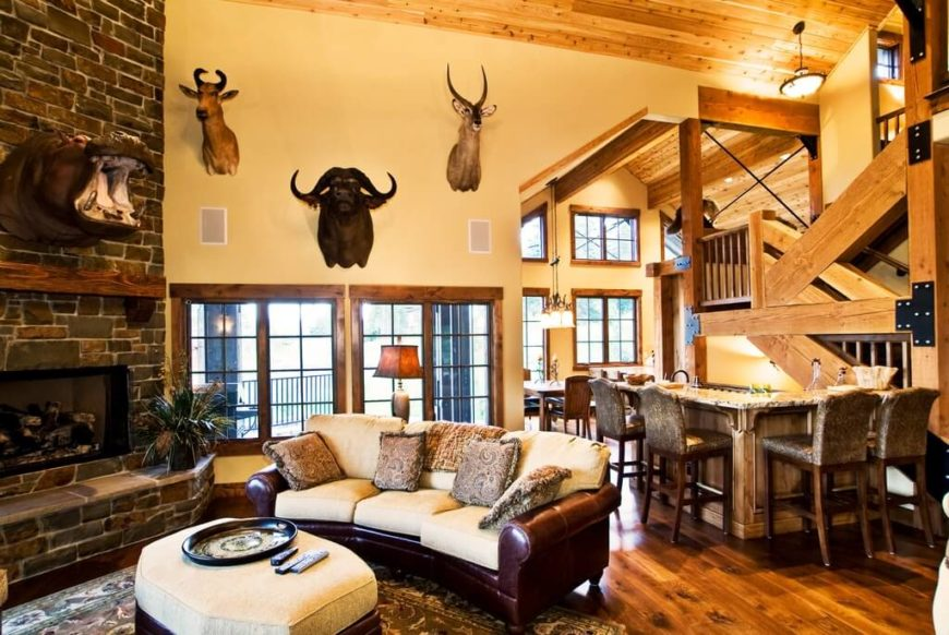 This large living room features a rustic country hunter design. With rich dark leather furniture and rich wood stain throughout. The walls are dotted with various animal mounts, strategically placed to leave no space barren in this living room.