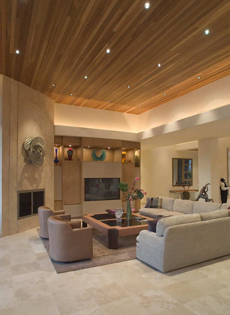 The large couch wraps around the edge of this living room, and acts as a containment factor for the area. The soft earth tones in this living room interact with low lighting to suggest comfort and a relaxed feel. The wall decorations accent the space and bring an aspect of artistry and color to the room.