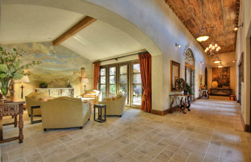 This grand living room opens up completely to a large hallway, and also features a large door leading out to the patio. Within the living room, large lounging chairs face each other in a circle, while the largest wall features a mural of a landscape and sky.