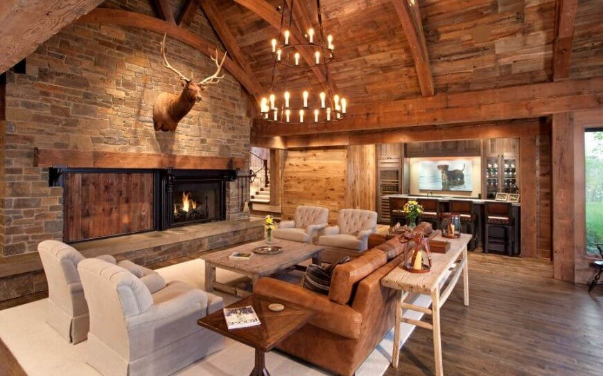 Natural wood grain is featured on the walls, ceiling, and floor in this living room. A leather couch sits before a smaller wooden coffee table, facing a large fireplace within a stone wall. A large animal mount above the fireplace is the focal point in this living room.