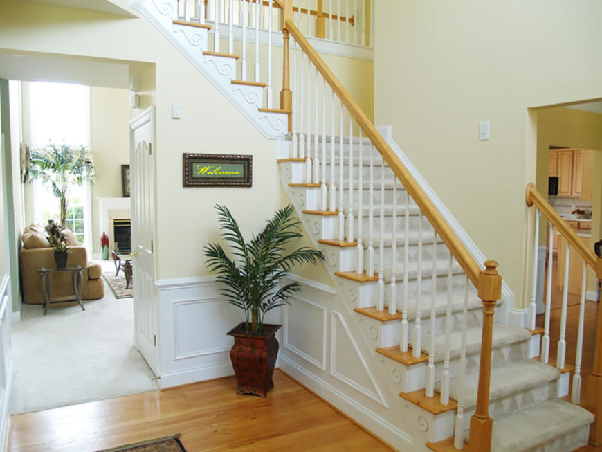 The pale, butter-yellow walls of this foyer acts as a bridge between the white of the wainscoting and the honey color of the wood accents.
