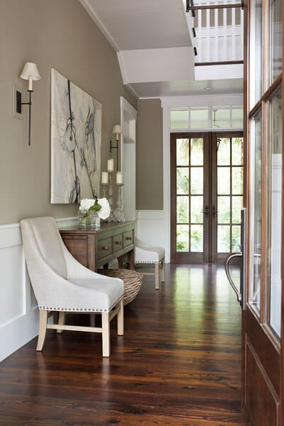 The gray walls are a perfect balance to the white trim and absolutely gorgeous wood floors. Creamy leather covers the accent chairs the flank the wooden side table present in the foyer. Lovely wall art brings the colors of the room together in one location.