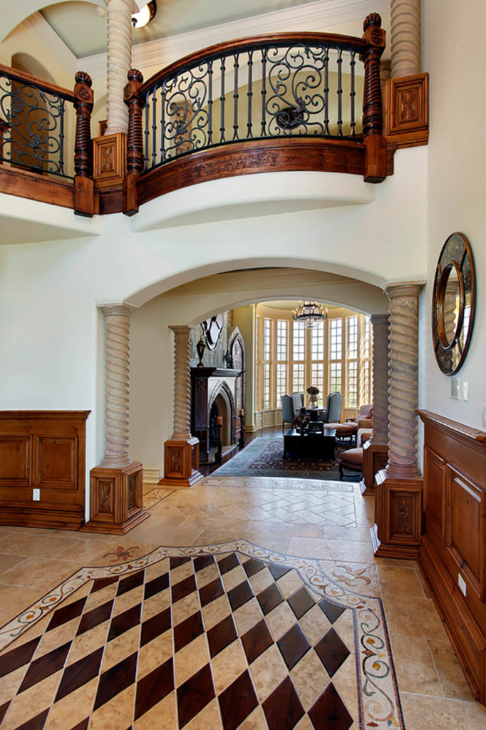 Rich wood wainscoting enhances the stately grandeur of this room. Bold patterns, ornate carvings, deep colors, and pillars all add to the historic luxury of this design. The wrought iron railings seen bordering the upper balcony continue this design up into the second floor.