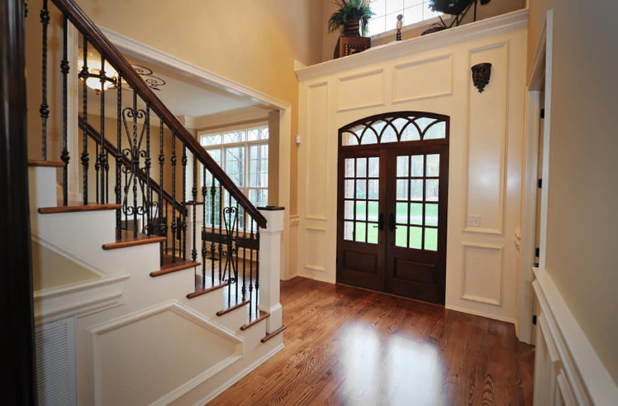 White wainscoting offsets the warm tan walls and dark wood used in the room. Black accents add depth and the ached shape of the front door sets it apart from the other, more structured arches in the home. Touches of color are brought into the room from the plants placed above the front door.