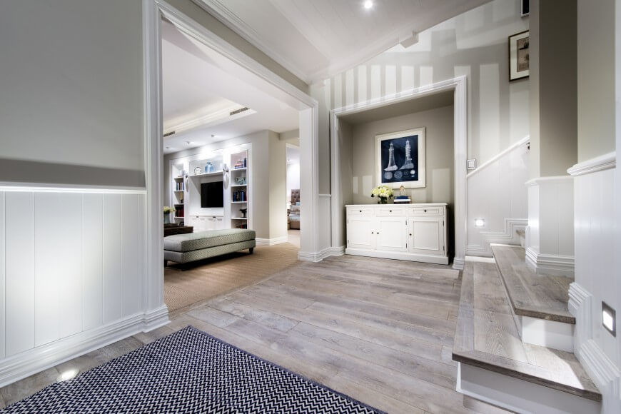 Pale, neutral tones are used throughout this home, but the addition of navy blue accents brightens up this entryway and brings touches of the nautical theme into this room. Light, weathered wood floors set the beach-y, nautical tone of the design while the simple white wainscoting enhances the room as a whole.