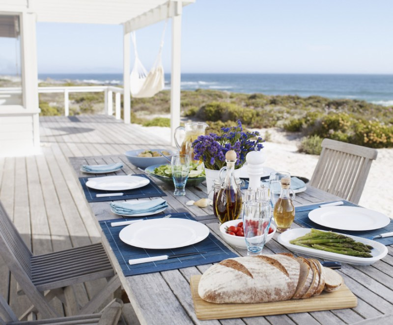 This table has a distressed and worn wooden look. This light and natural aesthetic replicates the feel of driftwood. It is the perfect look for a beachside deck.