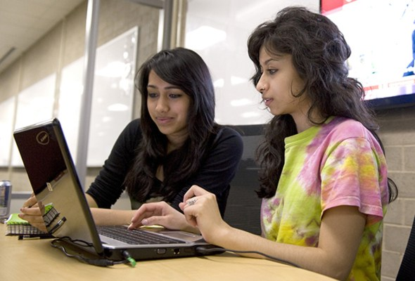 college students collaborating at a laptop computer