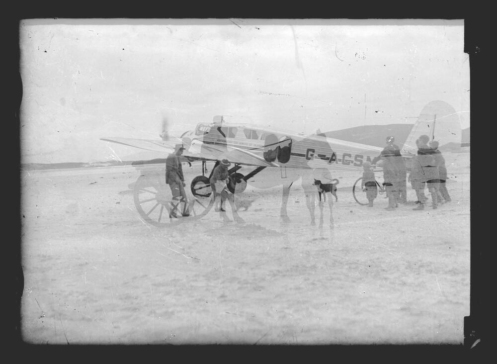 A black and white double exposed photograph. One layer shows a plane landing on a sandy beach with a group of people and a collie dog waiting nearby. The other, fainter image shows a horse and cart.